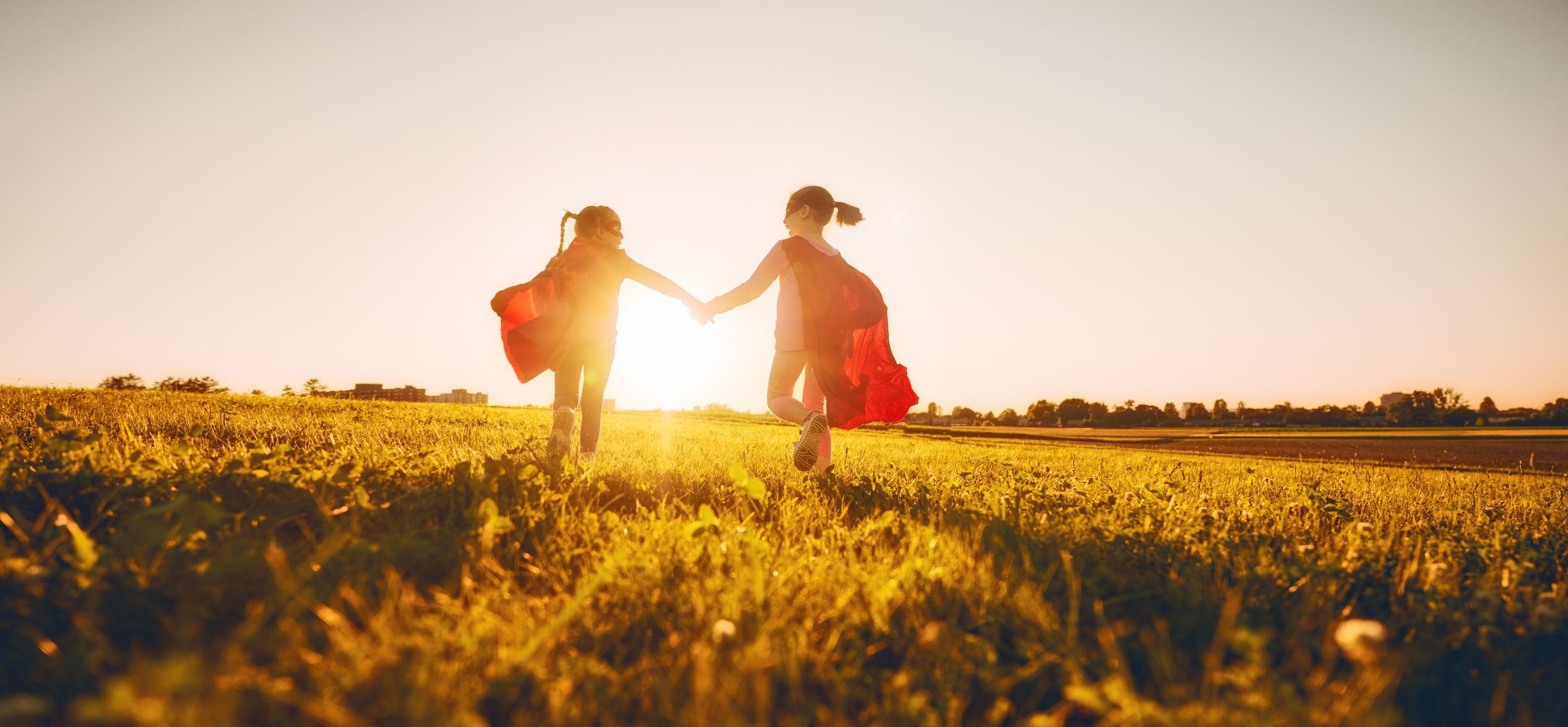Children Dressed as Superheroes Running Through a Field